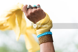 Person wearing blue and silver bracelet holding yellow textile