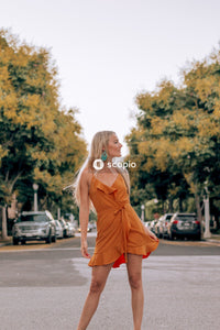 Woman in orange sleeveless dress standing on road