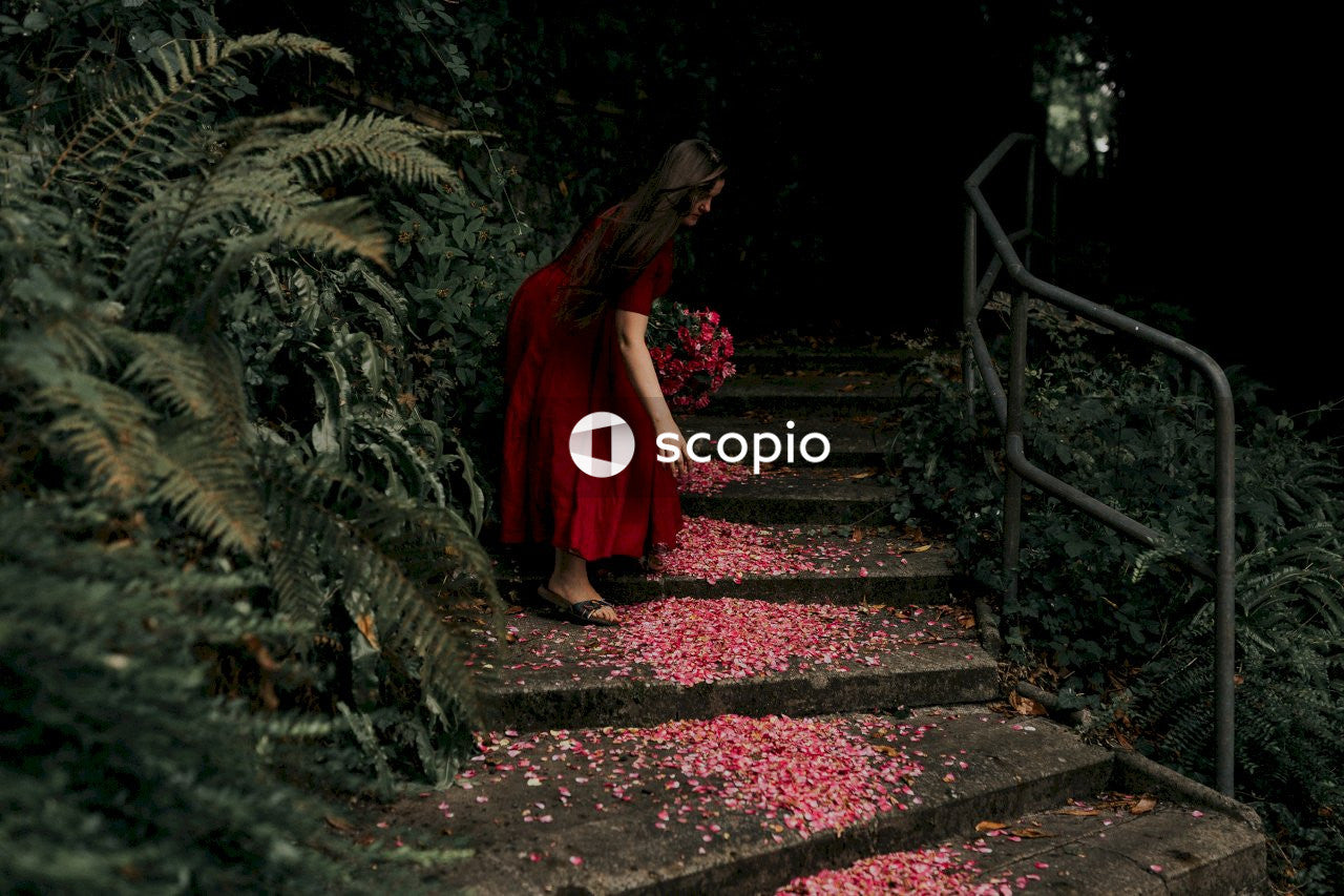 Woman in red dress standing on concrete staircase