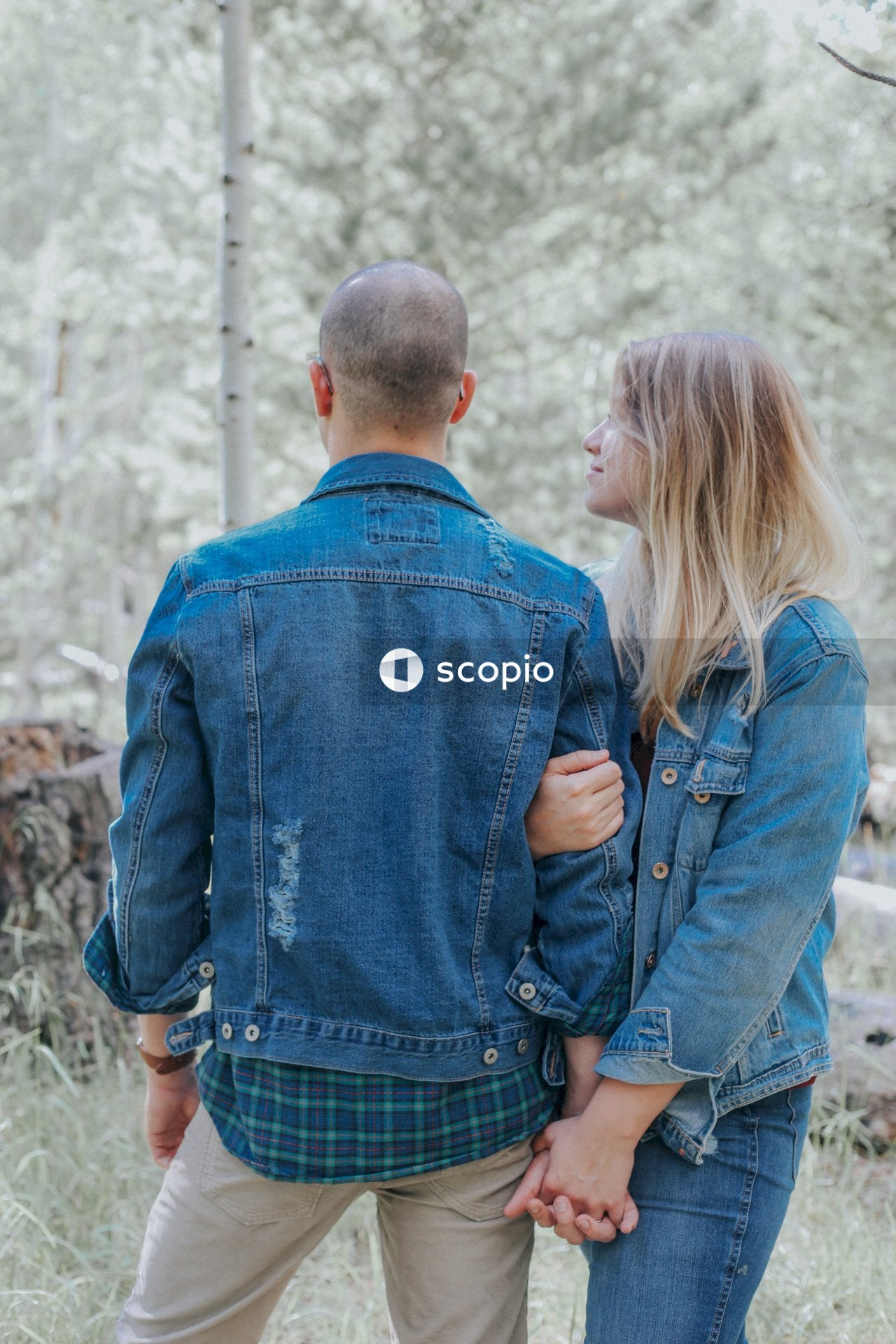 Man in blue denim jacket standing beside woman in blue denim jacket