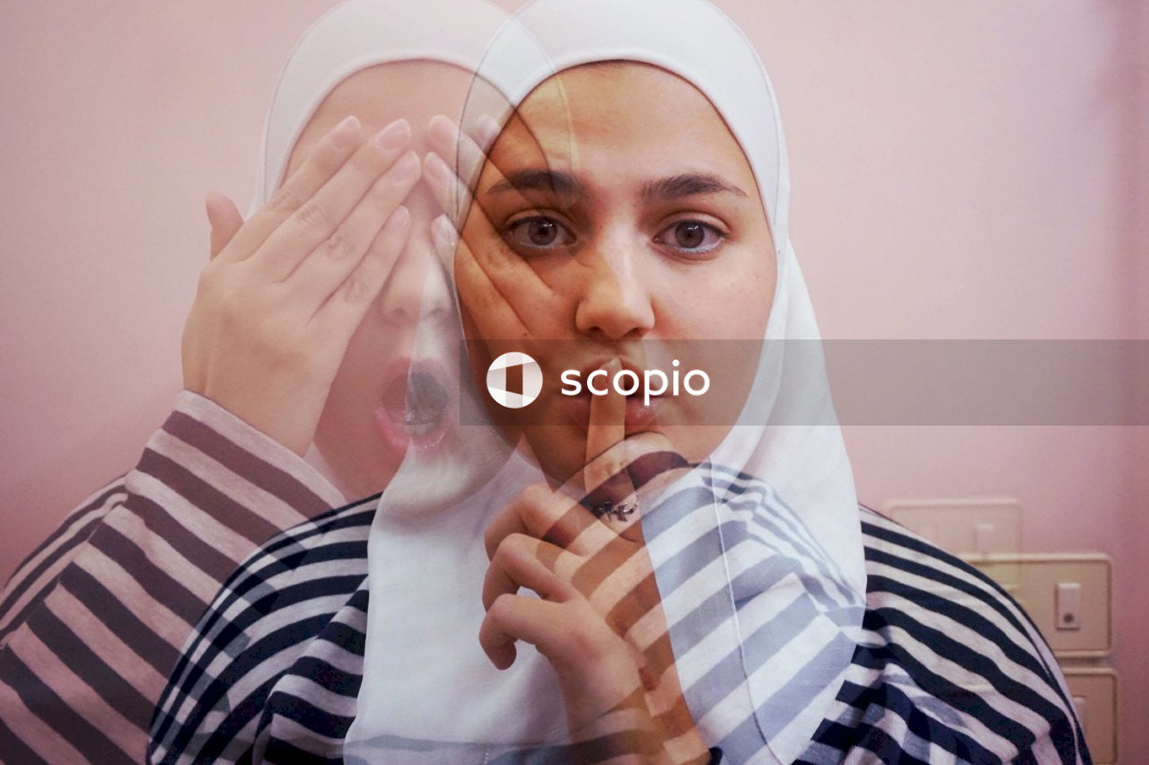 Woman in white hijab and black and white stripe shirt