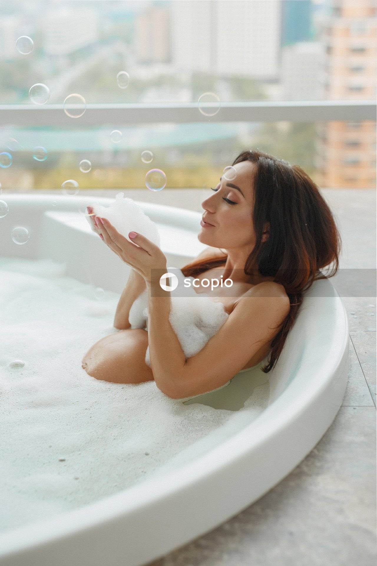 Woman inside bathtub playing bubbles