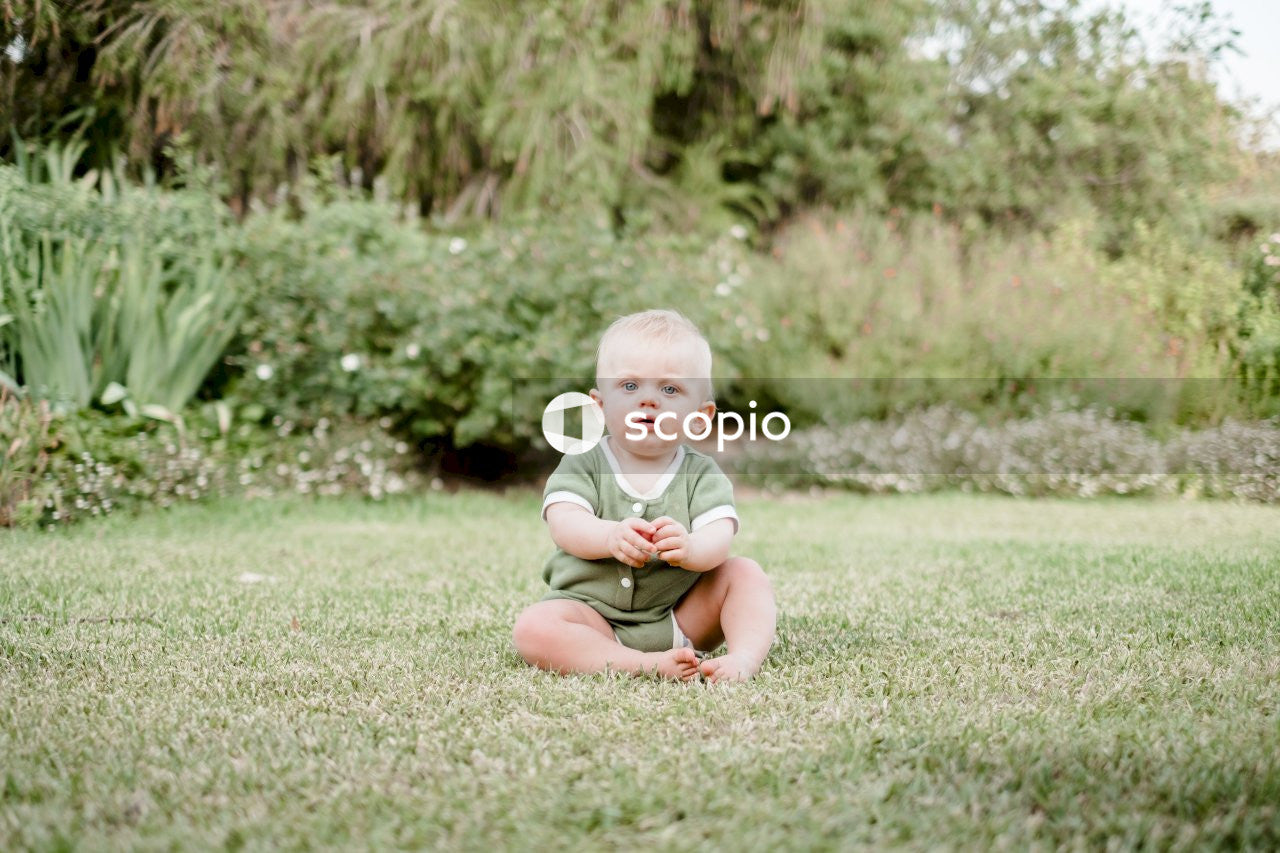 Baby in yellow tank top sitting on green grass field