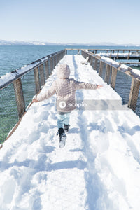 Girl in white winter coat and blue denim jeans walking on snow covered bridge
