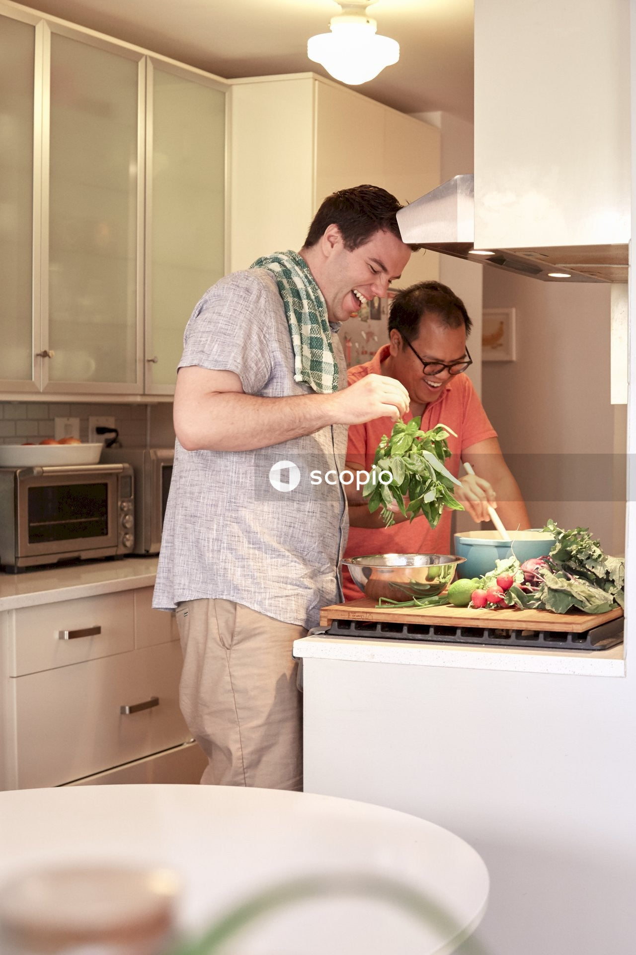 Gay couple laughing while cooking together at home