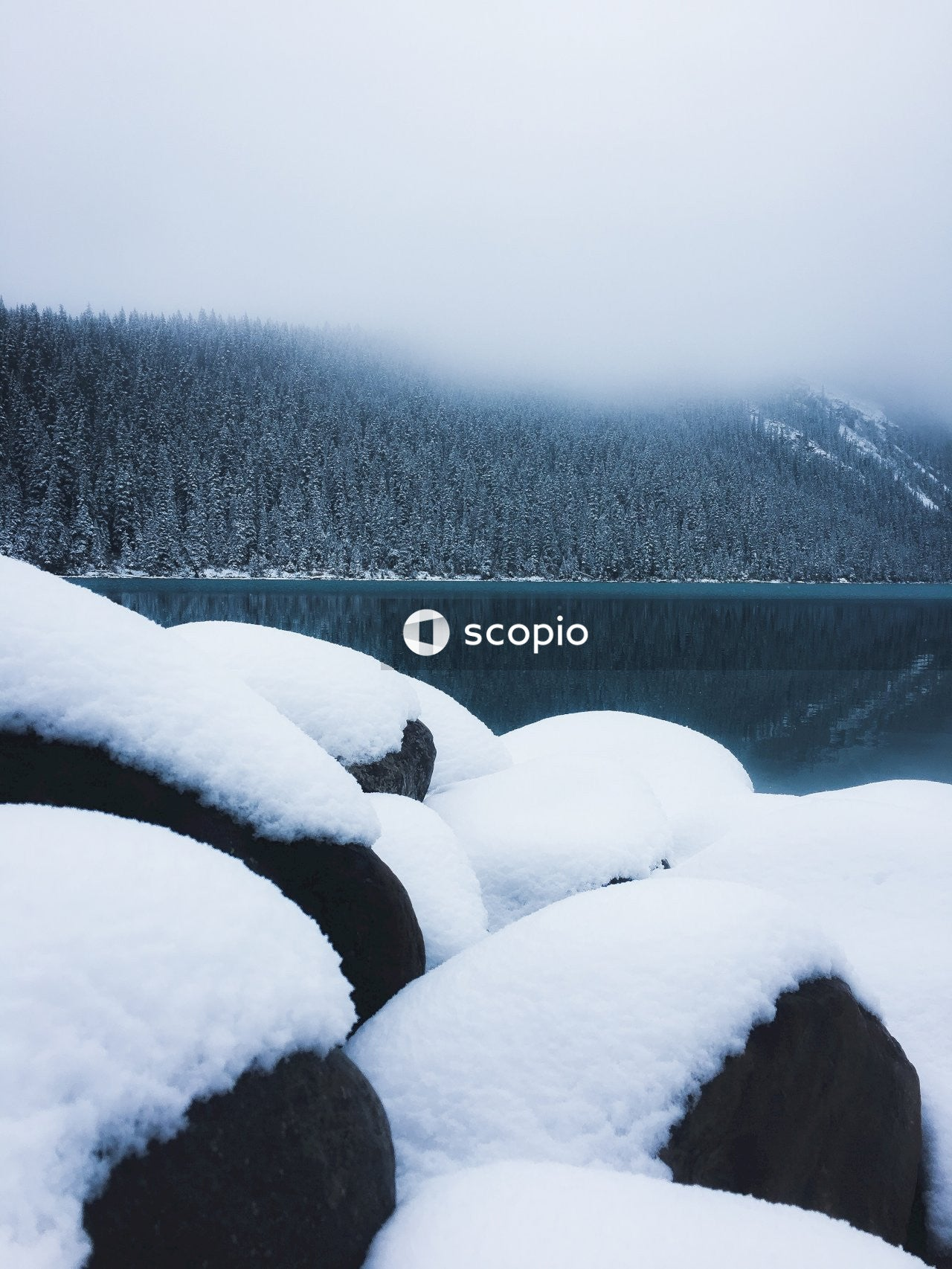 Snow covered rocks by lake and forested hill in fog