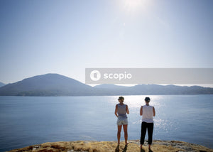 Two men standing on cliff looking body of water