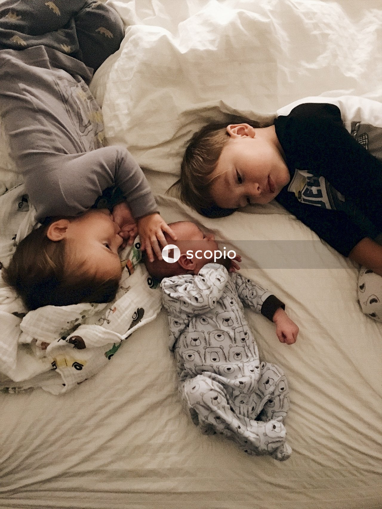 Three children lying in bed together