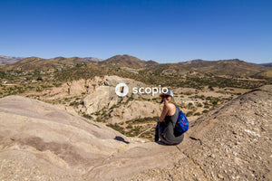 Man in blue t-shirt and black pants sitting on brown rock mountain