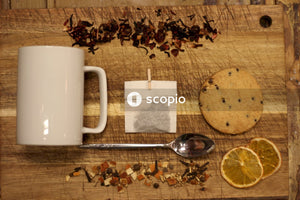 Stainless steel spoon beside white ceramic mug on brown wooden table