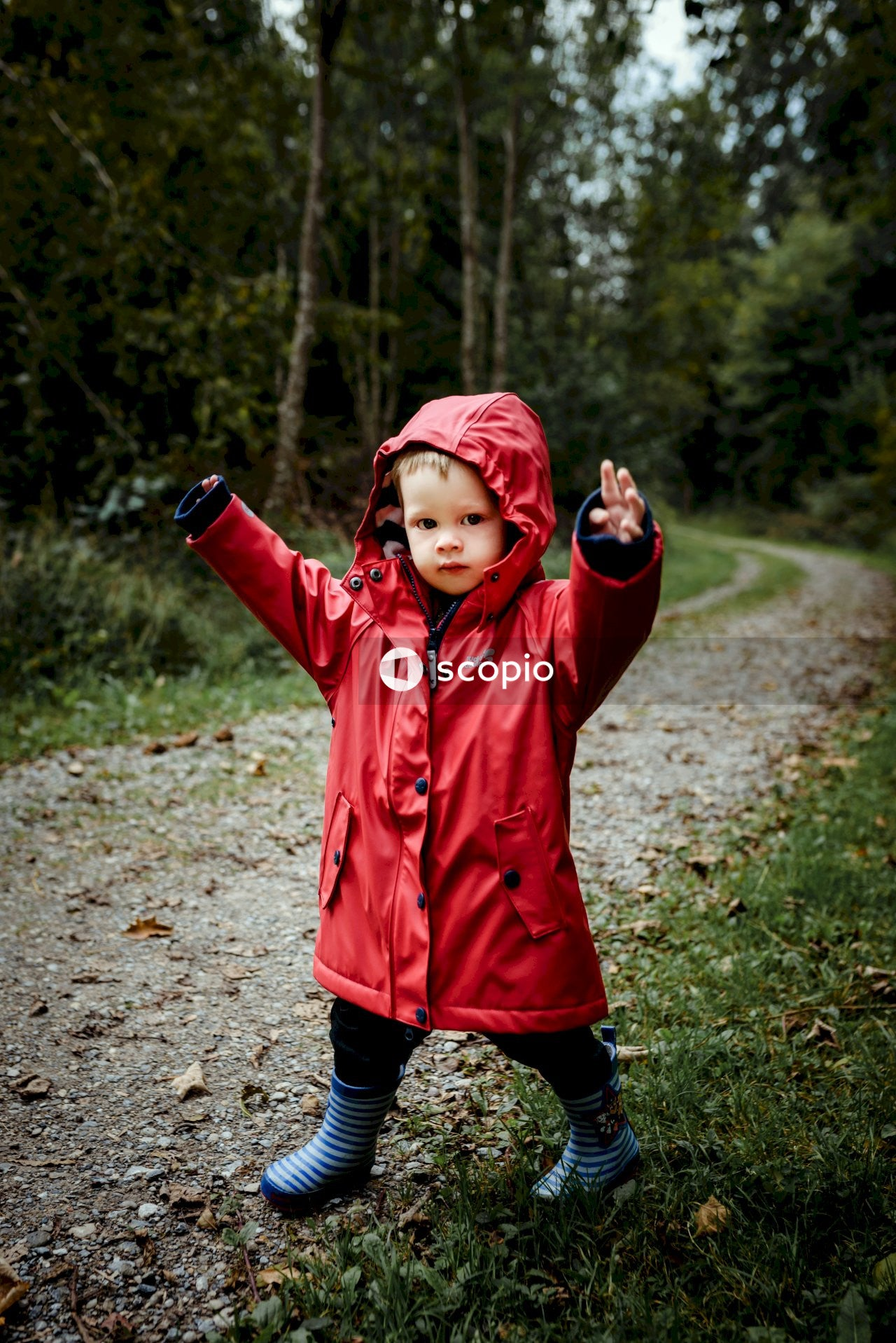 Girl in red jacket standing on dirt road