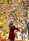 Girl in red long sleeve shirt standing under brown tree