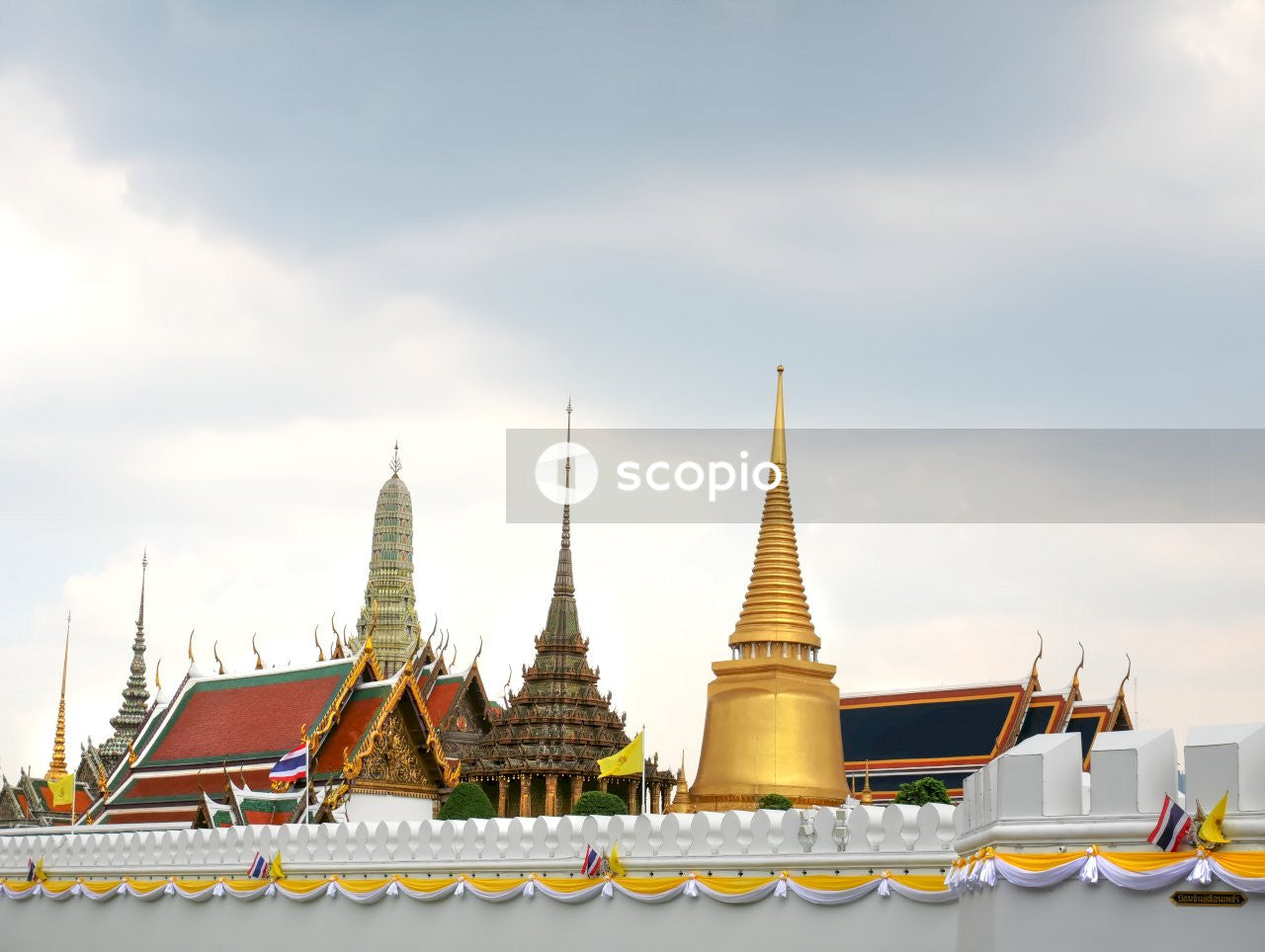 Gold and white temple under cloudy sky