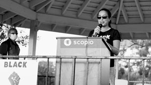 Grayscale photo of man in black t-shirt holding microphone