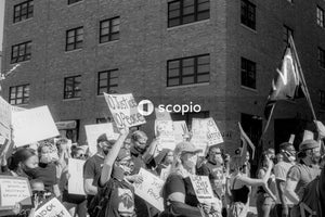 Grayscale photo of people holding banner