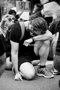 Grayscale photo of woman in black t-shirt and black shorts sitting on ground