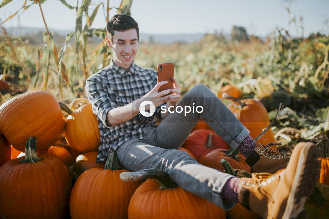Man in black and white plaid dress shirt sitting on pumpkin field