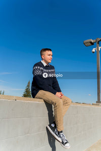 Man in black and white sweater sitting on concrete wall