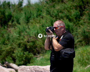 Man in black polo shirt holding black dslr camera