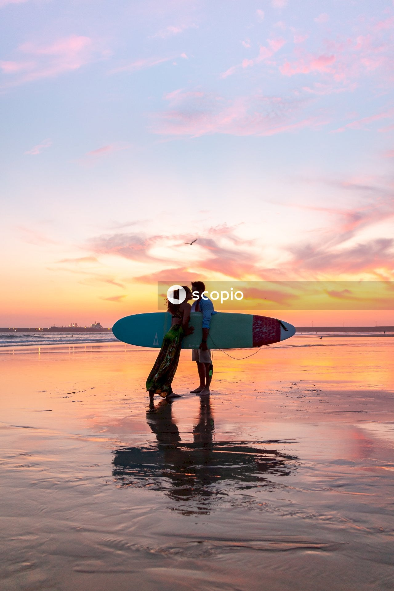 Man in black wet suit holding surfboard walking on beach during sunset