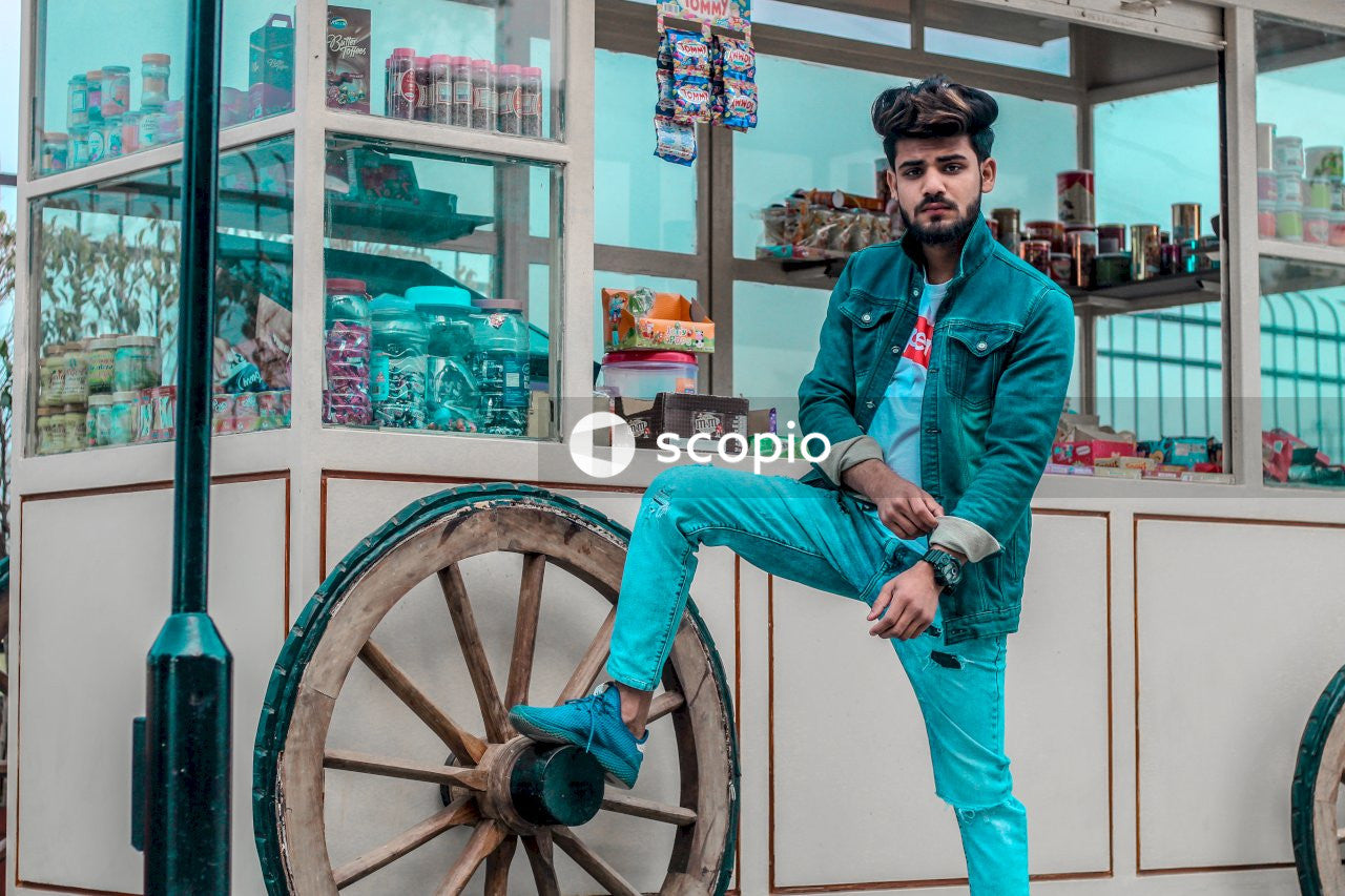 Man in blue denim jacket standing beside brown wooden wheel