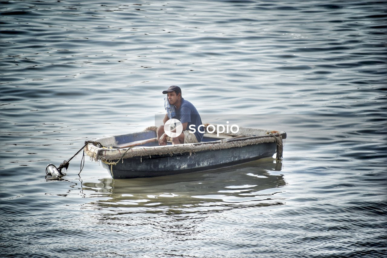 Man in blue shirt sitting on brown boat