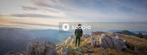 Man in green jacket standing on rock formation