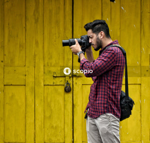 Man in red and black plaid dress shirt and white pants holding black dslr camera