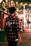 Man in red black and white plaid dress shirt standing on sidewalk during nighttime
