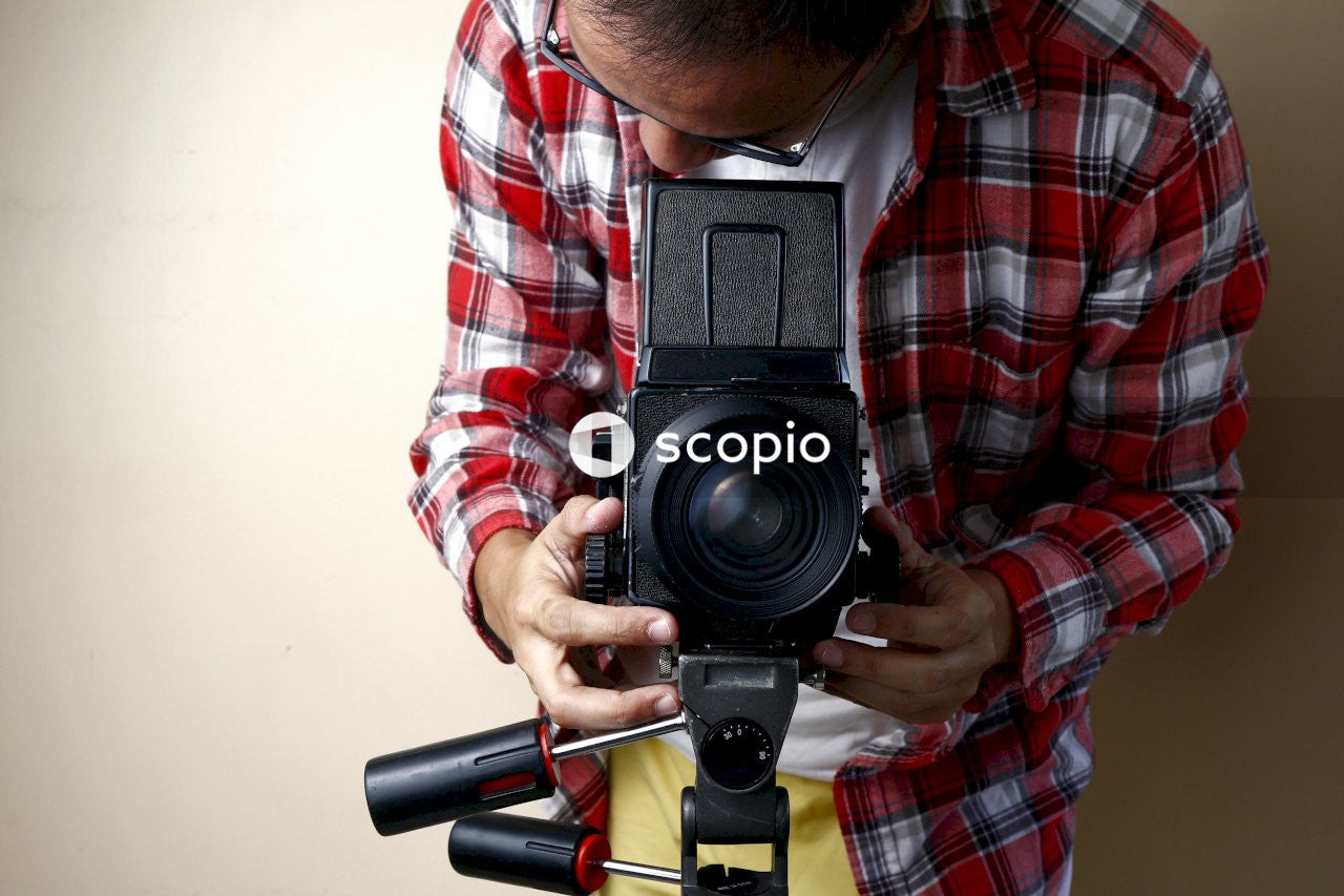 Man in red white and black plaid dress shirt holding black dslr camera