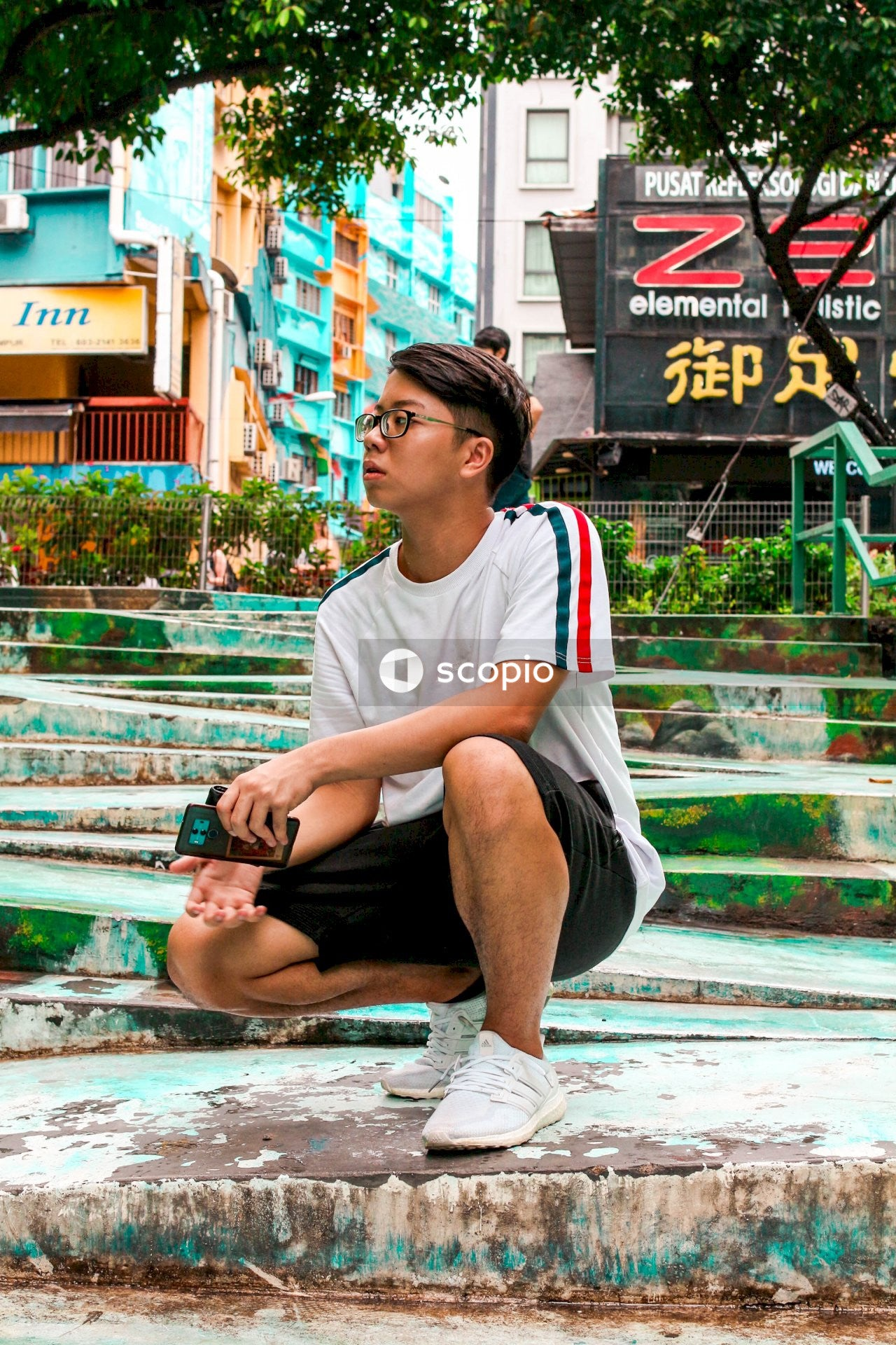 Man in white crew neck t-shirt and gray shorts sitting on green metal bench