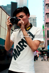 Man in white crew neck t-shirt holding black dslr camera