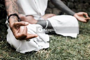 Man in white dress shirt and white pants sitting on green grass field