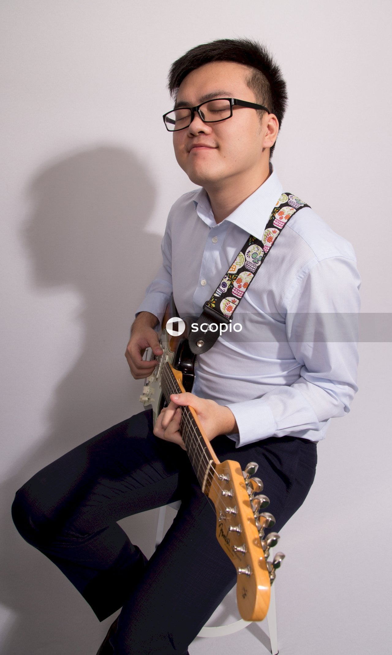 Man in white dress shirt playing brown acoustic guitar