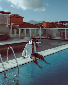 Man in white shirt and black shorts jumping on pool