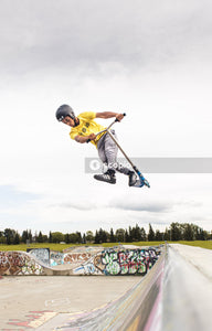 Man in yellow shirt and black pants wearing yellow helmet riding skateboard