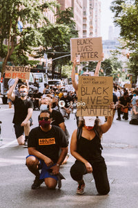 People holding brown wooden signage