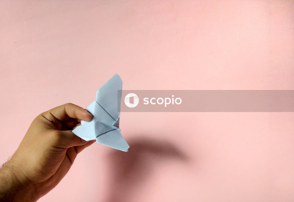 Person holding white paper plane