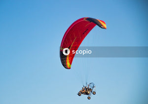 Person in red parachute under blue sky