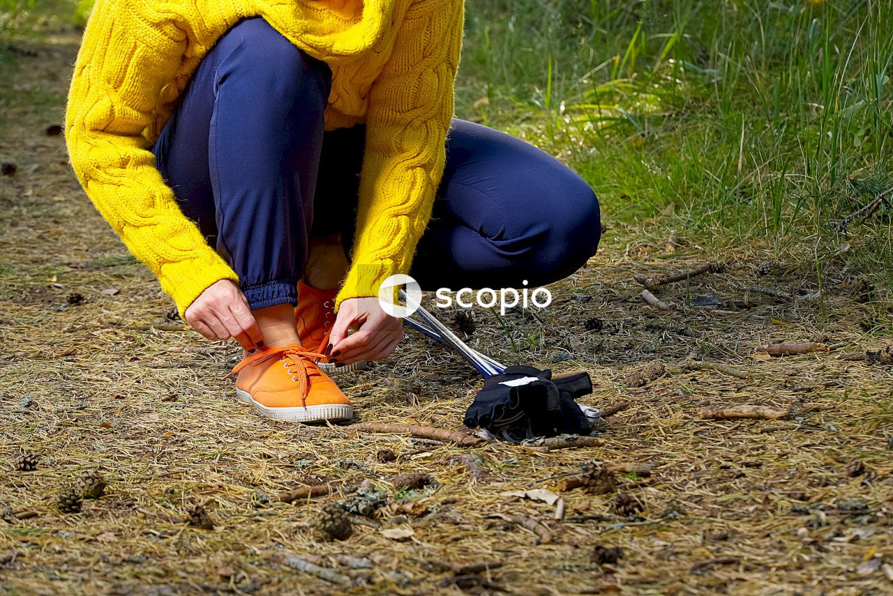 Person in yellow jacket and blue pants sitting on ground