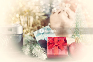 Camera beside gift boxes and Christmas bag
