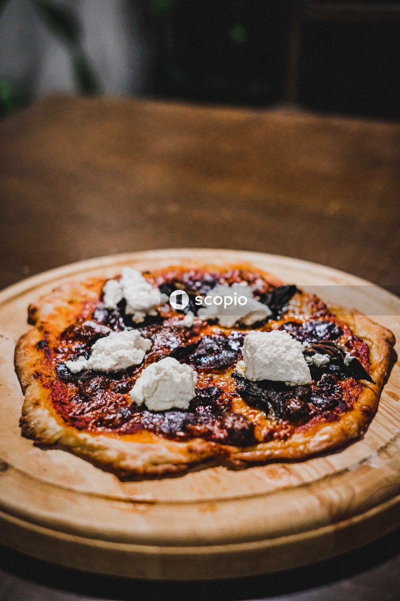 Pizza with white and black toppings on brown wooden table