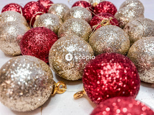 Red and gold baubles on white textile