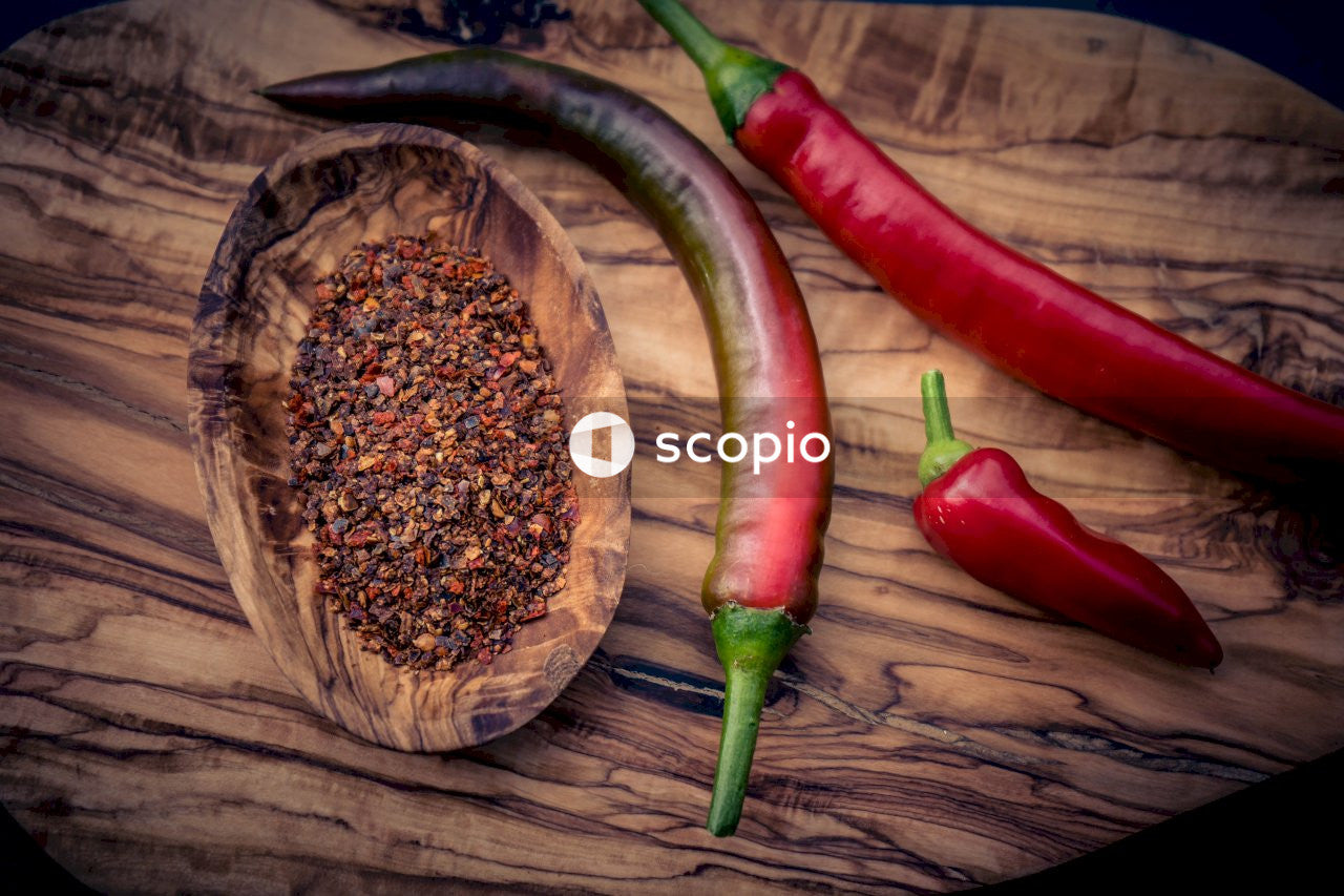 Red chili pepper on brown wooden round plate
