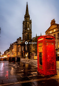 Red telephone booth in front of brown concrete building during night time