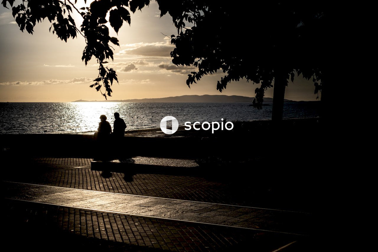 Silhouette of man and woman sitting on bench near beach during sunset