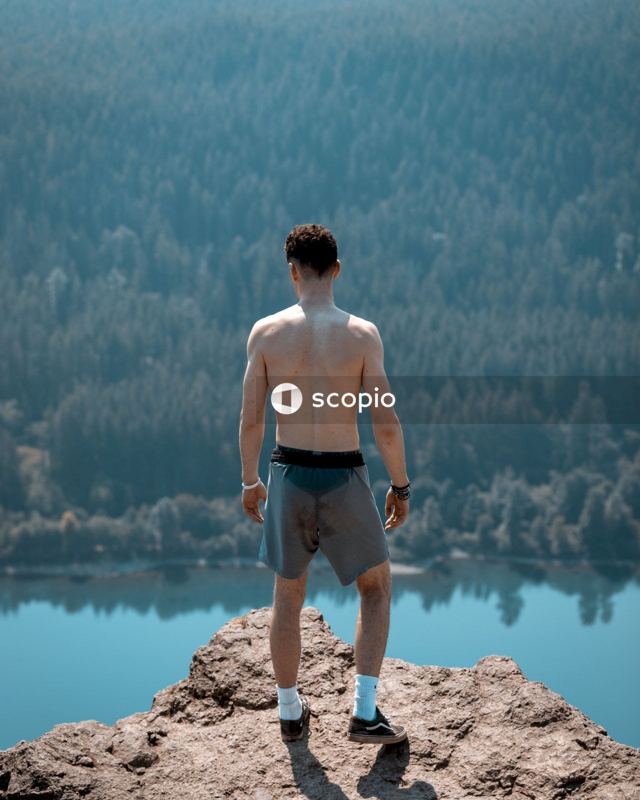 Topless man in black shorts standing on brown rock near body of water