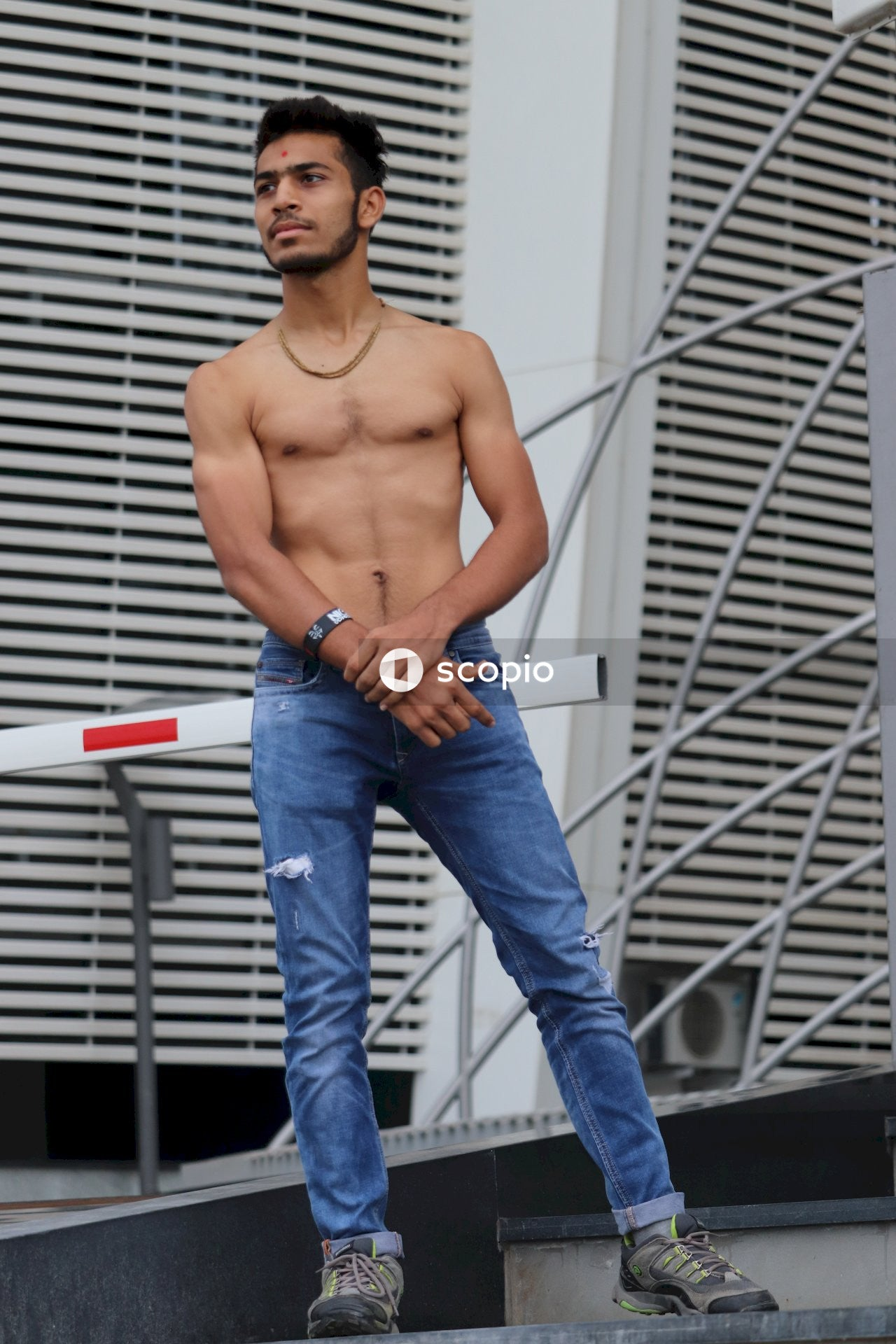 Topless man in blue denim jeans standing near white metal fence