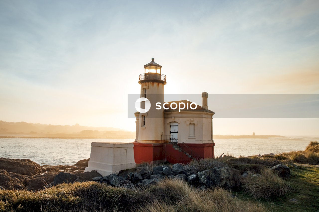 White and brown concrete lighthouse near body of water