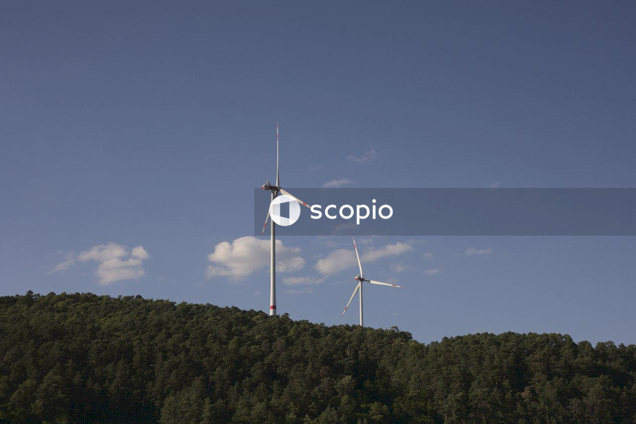 White wind turbine on green forest